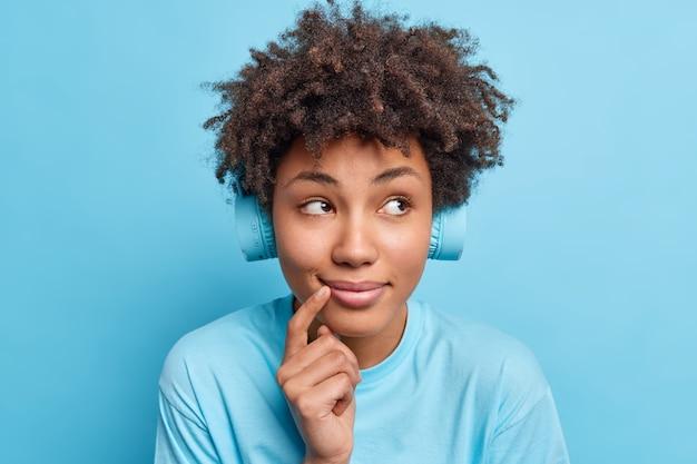 Gros plan d'une femme afro-américaine rêveuse souriante doucement concentrée pensivement de côté écoute les paroles de la chanson via un casque stéréo sans fil porte des vêtements décontractés isolés sur un mur bleu