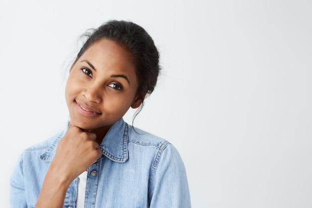Gros plan d'une femme afro-américaine avec des yeux chauds sombres et un sourire attrayant vêtu de vêtements décontractés posant sur un mur blanc. jolie femme à la peau foncée ayant un look heureux isolé sur blanc.