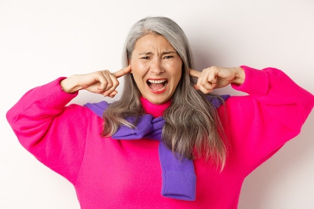 Gros plan d'une femme âgée asiatique agacée et dérangée criant avec les oreilles fermées, dérangée par un bruit fort, debout sur fond blanc