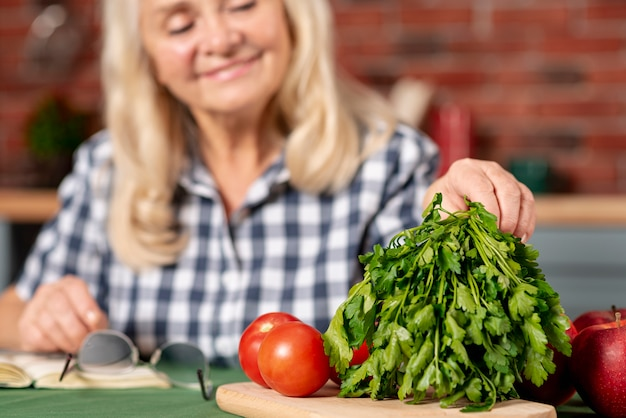 Gros plan femme âgée préparant des légumes