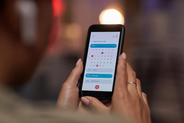 Gros plan de femme à l'aide du calendrier en ligne sur téléphone mobile pour planifier sa semaine