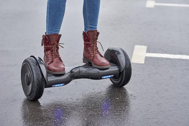 Gros plan de femme à l'aide de hoverboard sur route goudronnée. pieds sur scooter électrique extérieur