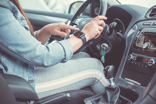 Gros plan d'une femme à l'aide d'une montre intelligente pendant la conduite de sa voiture, concept de transport