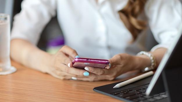 Gros plan sur une femme à l'aide d'un smartphone sur une table avec un stylet pour tablette sur une table en bois, vérifiant les actualités