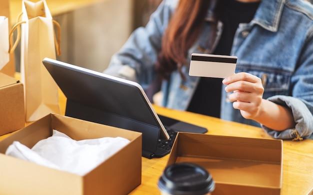 Gros Plan D'une Femme à L'aide De Tablet Pc Et Carte De Crédit Pour Les Achats En Ligne Avec Colis Postal Et Sacs à Provisions Sur La Table Photo Premium