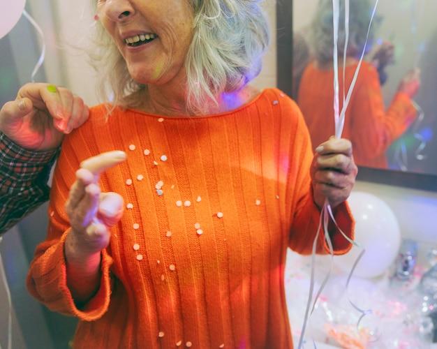 Gros plan, femme aînée, confettis, ballon, main