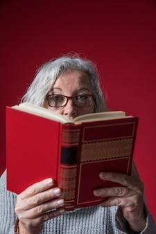 Gros plan, de, a, femme aînée, lecture livre, contre, toile de fond rouge
