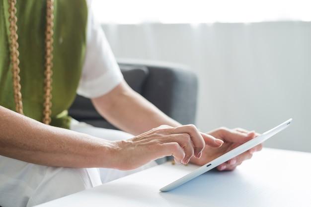 Gros plan, de, femme aînée, main, utilisation, tablette numérique