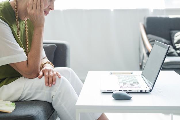 Gros plan, de, femme aînée, regarder, ordinateur portable, sur, table blanche