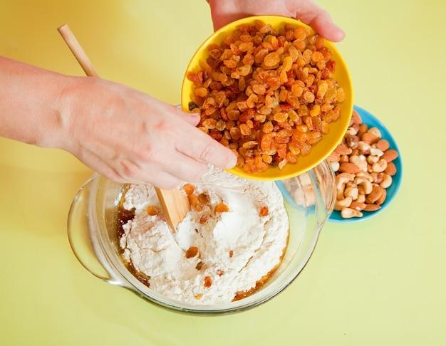 Gros plan de femme ajoute des raisins dans la pâte