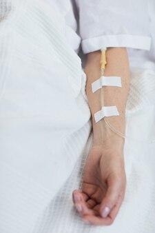 Gros plan d'une femme allongée sous un goutte-à-goutte à l'hôpital