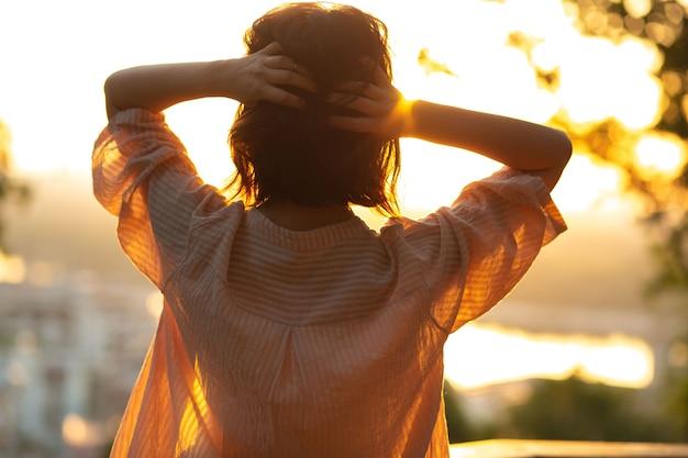 Gros plan d'une femme apaisée libre rencontre l'aube au parc
