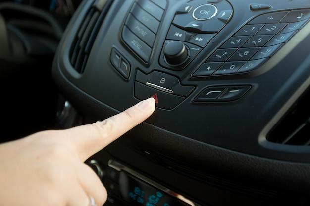 Gros plan d'une femme en appuyant sur le bouton d'urgence de la voiture