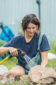 Gros plan de femme arrosant les plantes dans le jardin