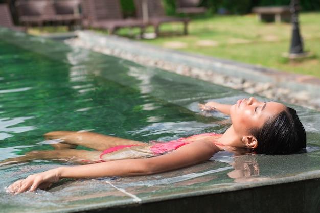 Gros plan de femme asiatique allongée sur l'eau au bord de la piscine