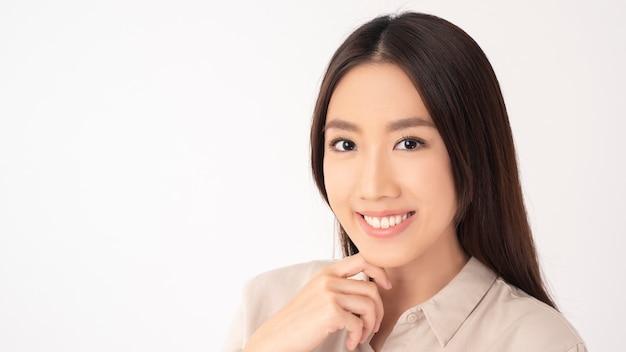 Gros plan d'une femme asiatique avec de belles dents sur le mur blanc