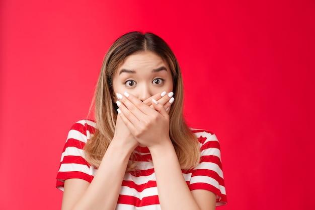 Gros plan femme asiatique choquée haletant sans voix presse mains lèvres lèvent les sourcils impressionné stupéfait sta ...