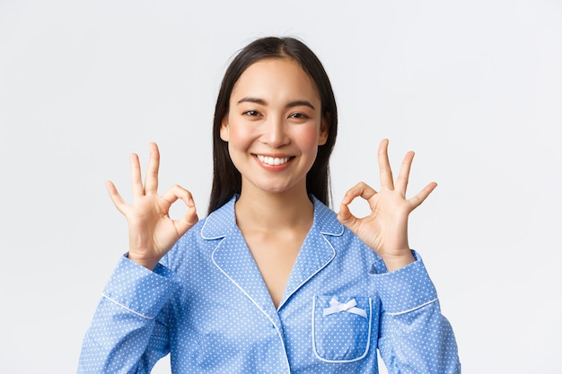 Gros plan d'une femme asiatique heureuse et satisfaite en pyjama bleu, taux de travail agréable, recommander une qualité de produit ou de service parfaite, garantir quelque chose comme montrer un geste correct heureux, fond blanc