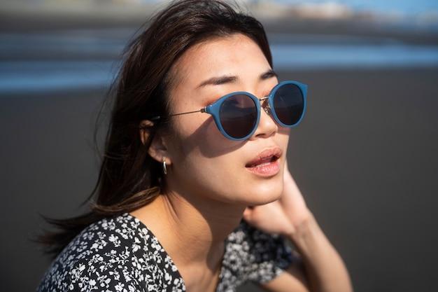 Gros plan femme asiatique avec des lunettes de soleil