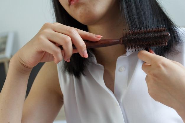 Gros plan d'une femme asiatique peignant les cheveux.