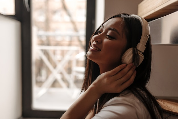 Gros plan d'une femme asiatique portant des écouteurs et un t-shirt blanc contre la fenêtre
