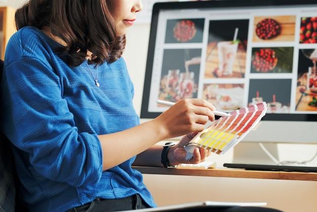 Gros plan sur une femme asiatique en pull bleu choisissant une palette pour la conception de sites web dans un bureau moderne