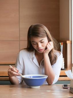 Gros plan femme asiatique s'ennuie visage à l'aide de baguettes pour manger des nouilles au restaurant.
