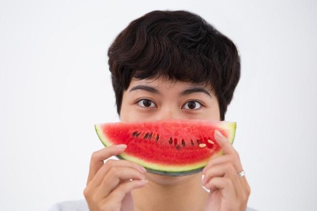 Gros plan de la femme asiatique sérieuse holding watermelon