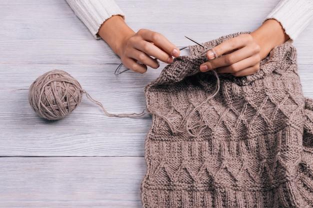 Gros plan d'une femme assise à une table en bois et un pull se tricote