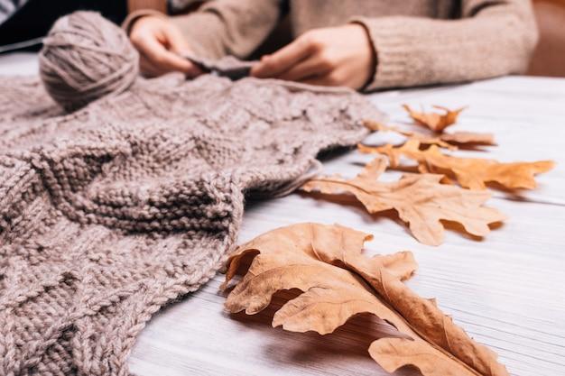 Gros plan d'une femme assise à la table en train de tricoter un pull en laine