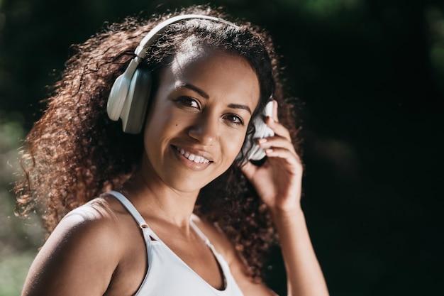 Gros plan sur une femme athlétique souriante portant des écouteurs