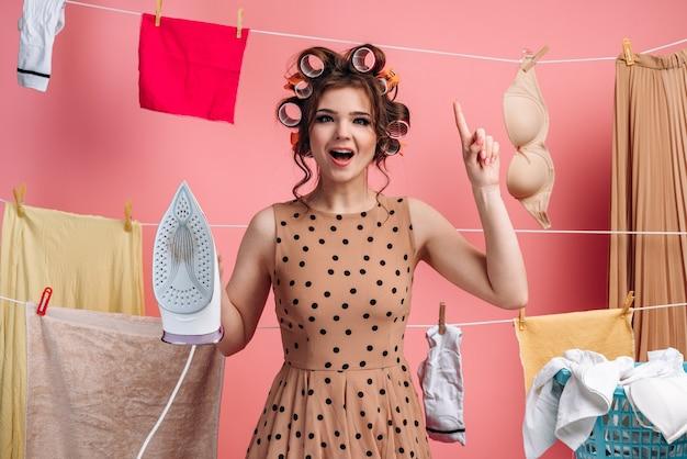 Gros plan femme au foyer dans une robe à pois a soulevé son index, a une excellente idée