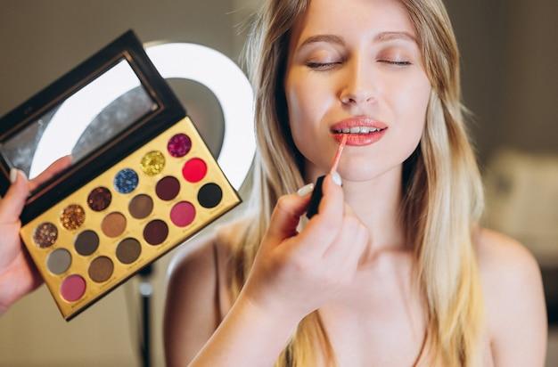 Gros plan d'une femme aux cheveux blonds et aux yeux fermés mis sur le rouge à lèvres. palette avec fard à paupières ou rouge à lèvres près du visage d'une belle femme.