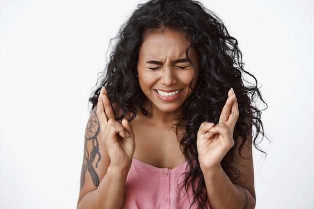Gros plan sur une femme aux cheveux bouclés anxieuse et inquiète avec des tatouages, louchant, serrant les dents nerveusement, croisant les doigts bonne chance, anticipant une chose importante, priant debout mur blanc