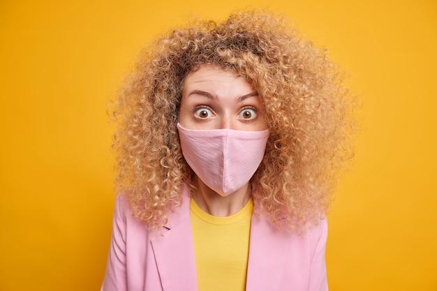 Gros plan d'une femme aux cheveux bouclés portant un masque de protection choquée par les restrictions de verrouillage et la quarantaine étendant les risques de propagation de l'infection vêtue de vêtements formels isolés sur un mur jaune