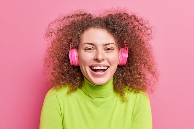 Gros plan d'une femme aux cheveux bouclés ravie qui rit en souriant largement a des cheveux touffus bouclés écoute de la musique via des écouteurs stéréo sans fil vêtus d'un col roulé vert isolé sur un mur rose