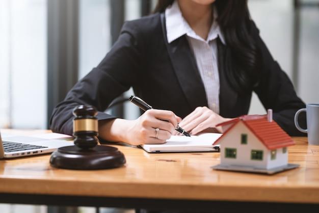 Gros plan sur une femme avocat tenant un stylo pour prendre des notes, des idées immobilières échantillon maison maillet vide au bureau.