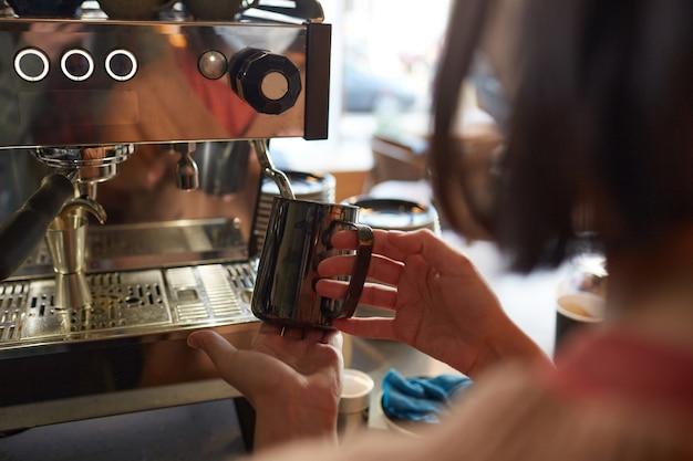 Gros plan sur une femme barista faisant du café frais dans un café ou un café et versant de la crème dans un latte, espace pour copie