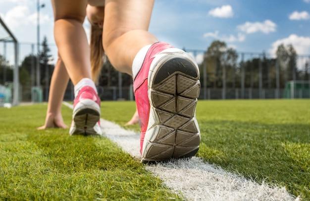 Gros plan d'une femme en baskets debout sur une ligne blanche dessinée sur l'herbe