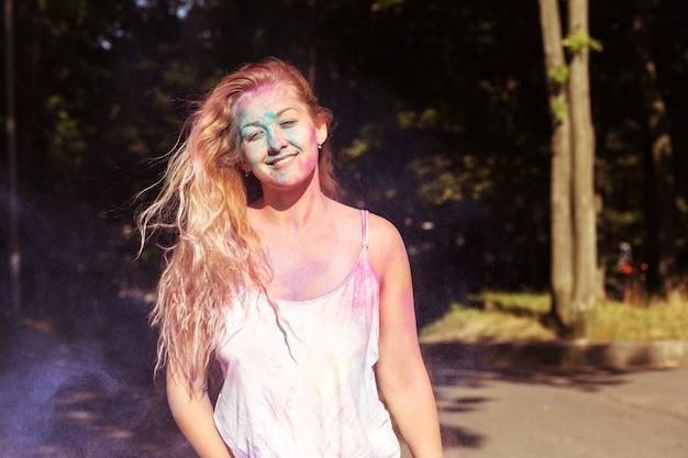 Gros plan d'une femme blonde joyeuse recouverte de peinture sèche colorée au festival des couleurs holi