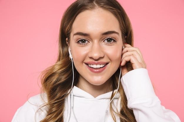 Gros plan, femme blonde souriante, vêtue de vêtements décontractés, écoutant de la musique et regardant l'avant sur le mur rose