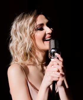 Gros plan d'une femme blonde tenant un microphone et chantant sur le fond noir isolé