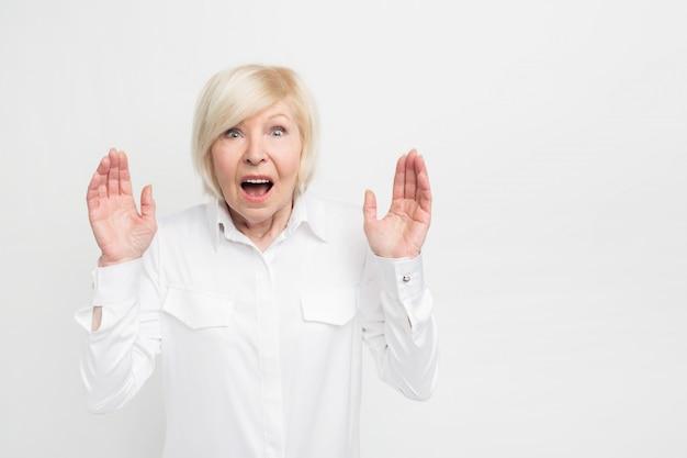 Gros plan d'une femme en blouse blanche debout sur le côté droit du cadre et montrant ses mains avec des cris. elle est sérieusement surprise.