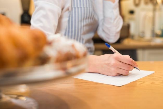 Gros plan, femme, boulanger, écriture, papier blanc, stylo, dessus, table bois