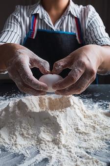 Gros plan, de, femme, boulanger, mains, casser, oeuf, dans, pâte crue