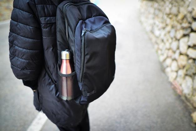 Gros plan d'une femme avec une bouteille d'eau dans un sac à dos. bouteille d'eau thermo en acier eco.