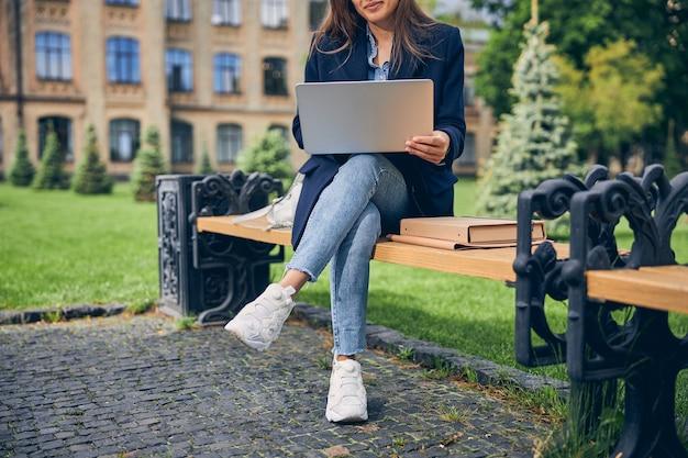 Gros plan sur une femme brune assise sur un banc avec son gadget et profitant du beau temps