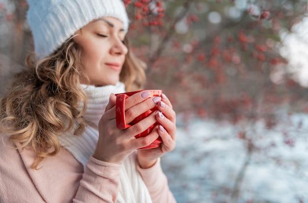 Gros plan femme brune bouclée tenant une tasse de boisson chaude en plein air
