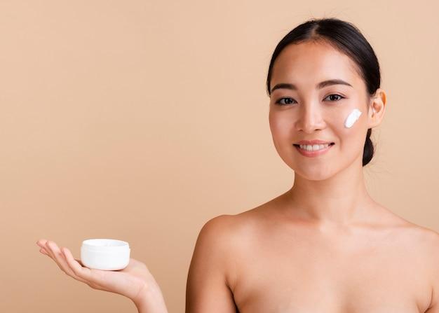 Gros plan femme brune avec une crème pour le visage