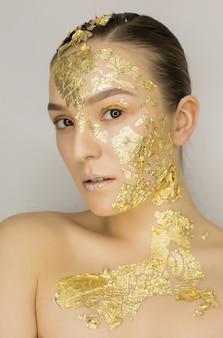 Gros plan d'une femme brune élégante avec un maquillage créatif de feuille d'or